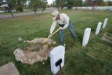 "Cemetery caretaker Frank ""Pancho"" Herrera (cq) tamps down dirt at the gravesite of..."