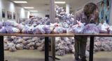 JPM142 Junior volunteer Bryan Graham, a senior at Denver Academy, waits amid bags of fruit and...