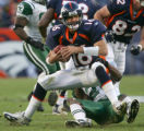 Jake Plummer is sacked by Kerry Rhodes in the 3rd quarter of the Denver Broncos against the New...