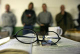 Reading glasses lay on top of an open Bible as residence line the outer edge of the mess hall...