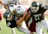 Alamosa quarterback Clay Garcia, center, is tackled by Niwot defenders Nathan Dorzweiler, left,...