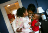 Latrieza Elzy, cq, center, plays with her stepdaughter, Kaelyn Elzy, 3, cq, left, and her nephew,...