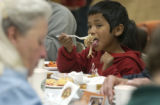 (CENTER) Jesus Dominguez, 7, of Fountain, enjoys some of the 220 turkeys donated by and prepared...