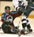 Colorado Avalanche player Brett McLean, left, tries to knock the puck out of the reach of...