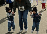 Twins Collin and Tyler Manuello, left and right, run with their mom Marcie Manuello (cq) in the...
