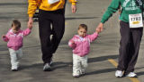 Twins MorenTuell, holds dads hand, Trevor Tuell, and Taiten Tuell, holds moms hand, Melissa Tuell,...
