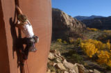 Climber Malynda Madsen of St. George jams an unnamed windgate sandstone handcrack with fall leaves...