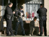 Denver Police Officers (far left and right) assist Officer Lucas (no first name given), center...