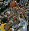 Nuggets guard Andre Miller is swarmed by New Orleans/Oklahoma City Hornet player Desmond Mason,...