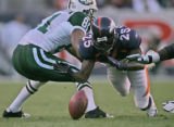 Denver Broncos safety Nick Ferguson,right, slips around Jets player Justin McCareins, left, as he...