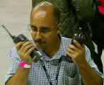An unidentified official uses two radios in this image captured from a DVD showing a recent...