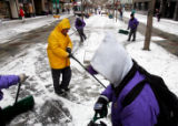 Workers from the Business Improvement Development shovel snow on the 16th Street Mall on Tuesday...
