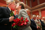 Pearl Harbor survivor David Wilson, cq, left, 85, receives roses and a kiss from Patricia...