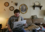 [JD134] Leslie Sheeder (cq), of Adel, Iowa, reads the front page of the Des Moines Register on...