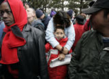 Sarah Estrada (cq), 15, keeps her brother Josh Trujillo (cq), 9, warm while they wait outside the...