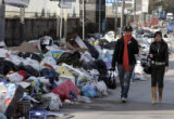 NAP102 - Two women walk past garbage heaps in Naples, southern Italy, Wednesday, Jan. 2, 2008....