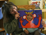 Leah Ross (cq) reads a book with her one year old son, Elijah Ross, in daycare, Thursday morning,...