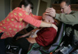Nurse Liz Bell (cq), left, helps her patient Scott Slade (cq) get positioned correctly in his...
