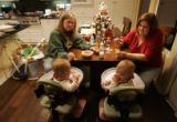 Kathy Slade (cq) feeds her twin daughters Samantha, left, and Stephanie, eleven months, with the...