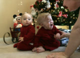 Samantha and Stephanie Slade, 11 months, are positioned for a Christmas photo December 9, 2007, by...