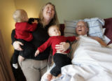 Kathy Slade (cq) holds her twin daughters, Samantha, left, and Stephanie, 11 months, while her...