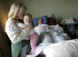 Kathy Slade (cq) gives one of her twin daughters Stephanie, eleven months, a kiss while her...