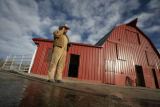 Joe Freund makes calls by his cattle barn at the Running Creek Ranch as the crew gets ready for...
