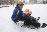DM0177   Chris Toll rides a sled with his son Harrison Toll, 8, at Governor's Park in Denver,...