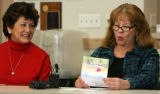 L to R: Card designer Mary Landis (cq) listens as card verse author Lenora Lovett (cq) reads a...