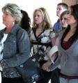 Alison Paige Bowen, 16, center, in black and white blouse, walks behind her mother,  holding hands...