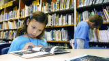Sara Feltz (cq), nine years old, reads a book in the school library Monday morning October 10,...