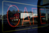 "A trailer truck drives by a ""CAFE"" sign on one of the windows at the Good Sheppard Inn..."