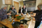 Residents gather around the kitchen island to fill up their plates at a potluck brunch in the...