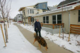 Silver Sage resident Susan Booker walks a neighbor's dog around the block of the co-housing...