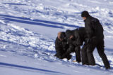 DM0162   Denver Police investigators  dig slugs out of the snow covered hillside in front of a...