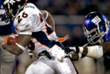 The Denver Broncos' Tatum Bell (#26, RB) eludes the grasp of the New York Giants' Justin Tuck...