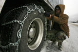 DM0556    Florida truck driver Jeffrey Mount chains up his rig on Interstate 70 on the approach up...