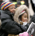 Wanda Monroe holds her 10 year old daughter Deja Monroe as they listen to speakers remember the...