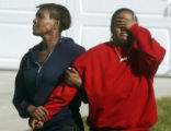 Macoya Harris (cq) covers her face after learning her aunt was found dead at a homicide scene at...