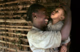 Beletech holds her son, Almaz, 7 months and laughs outside her tukul in Yetebon, Ethiopia. They...
