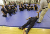 Recruiter Police officers look on as instructor, Don James, right, places Alfred Roberson, face...