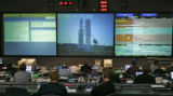 Lockheed Martin engineers and employees, monitor the final launch of a Titan IV rocket being...