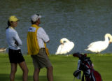 Michelle Wie (left) waits with her caddy, Jimmy Johnston (right) to continue play on the 18th hole...