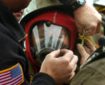 (DENVER, Colo., June 15, 2004)  Antoinette Torres-Janke gets help with her fire fighting gear from...