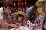 "Sheila Shea(cq), left, helps Emily Bennigsdorf(cq), 9, make a potpourri at a ""A Very Violet..."