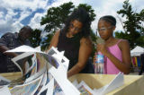 Christina Mullins (cq), left, and her daughter Lena Pleas (cq), 9, look through posters at the...