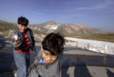 Momin Khan, 9, left, cq, throws a snowball at his brother, Musab Khan, 6, cq, at the top of...