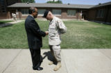 Tino Vasquez (cq), left, father of Justin Vasquez, shakes hands with Staff Sgt. Andy Yoder, after...