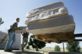 (L-R) Robert Wilson (cq) and Craig Clark  (cq) civilians , unload mattresses that are being put in...
