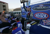 Funny Car winner Robert Hight holds aloft his first place trophy after winning on the final day of...